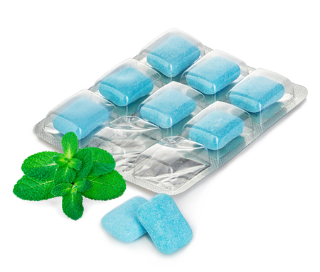 gum: Chewing gum in blister with mint leaves close-up on a white background Stock Photo