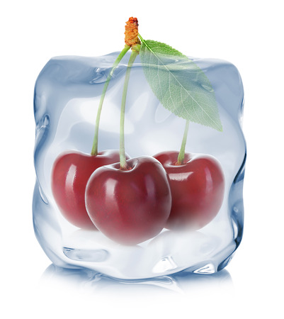 refrigerate: Cherries frozen in the ice cube close-up isolated on white background.
