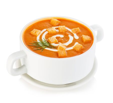 Delicious pumpkin and carrot soup with sour cream and croutons close-up isolated on a white background.