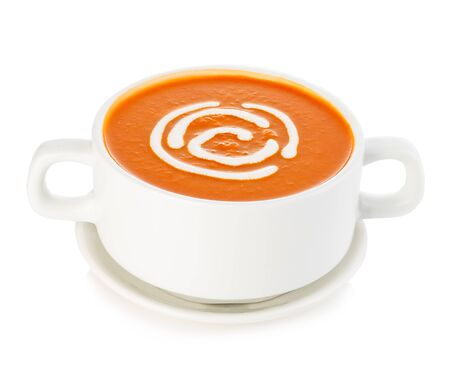 Delicious pumpkin and carrot soup with sour cream close-up isolated on a white background.