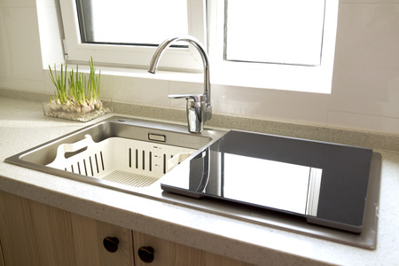 Luxurious modern kitchen with sink, Contemporary kitchen unit with chrome water tap. Decor with plant. Window with bright sun light.