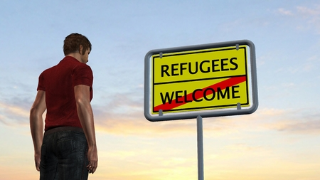 frontier: young man in front of Refugees Welcome Sign
