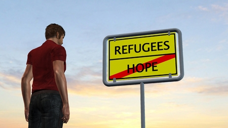 humane: young man in front of Refugees Hope Sign Stock Photo