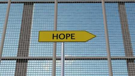 immigrant: Hope Signpost on metal fence border fence Stock Photo
