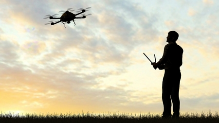 remote view: one operating of flying drone Quadrocopter UAV at sunset
