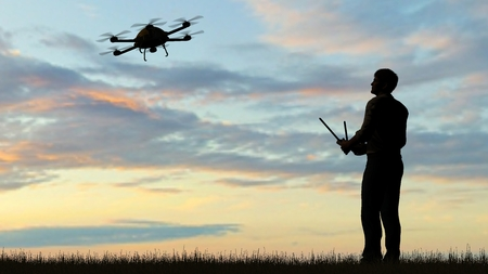 one operating of flying drone Quadrocopter UAV at sunset