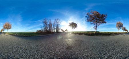 360 degrees spherical panorama of a asphalt country road with trees at late afternoon in autumn - germany Stock Photo