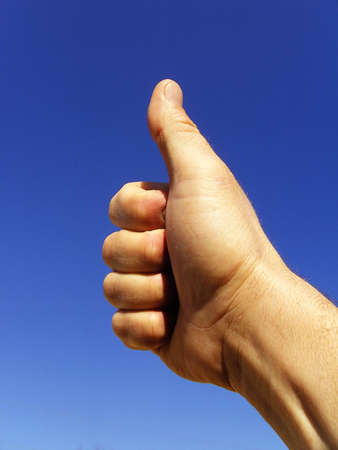 male hand with a thumb up against clear blue sky photo