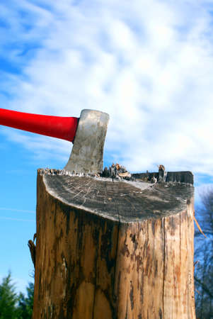 Axe in a splitting log against beautiful blue sky with fluffy clouds photo