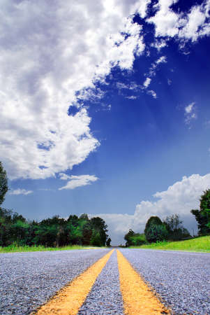 dramatically: Country-road with trees and bushes under a dramatically lighted sky Stock Photo
