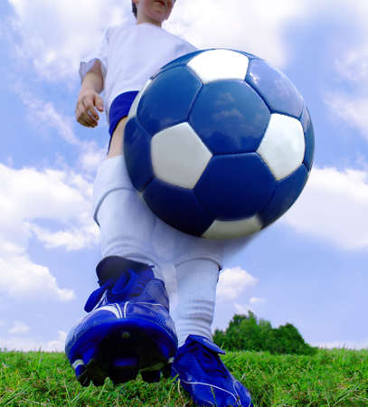 soccer cleats: Boy with cleats kicking soccer ball on green field with