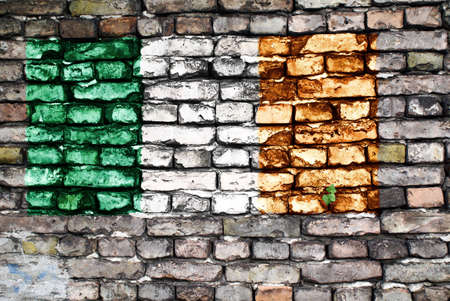 Flag of Ireland on an old brick wall with small ivy plant growing out of a crack. photo