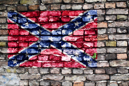 Flag of the Confederate Army painted on an old brick wall with small ivy plant growing out of a crack. photo