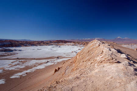 Beautiful Landscape of Salt deposits crossed by a road. Mountain formations were weathered by winds and rains. Taken during over the centuries at 2471.5 msm altitude at Valle de la luna at Calama - San Pedro de Atacama, San Pedro de Atacama in Antofagasta region (CHILE)