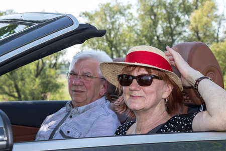 Older couple in a luxury convertible car on a sunny day Imagens