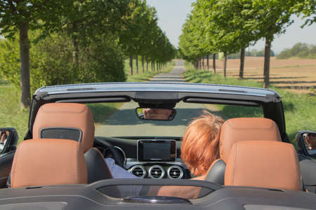 Older couple in convertible car enjoying day trip Imagens