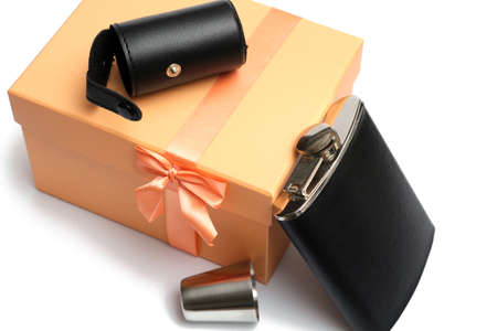 small leather hip flask with metal mug at orange giftbox on a white background
