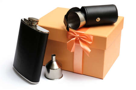 small leather hip flask with metal mug in cover at orange giftbox on a white background