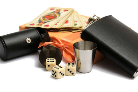 small leather hip flask with two metal mugs and three cubes and old playing cards at orange giftbox on a white background