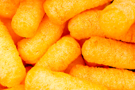 Cheese puff. Cheese puffs snack background texture food pattern.