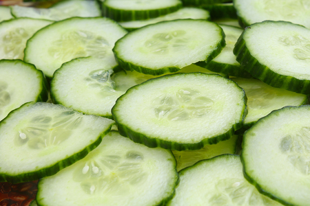 Cucumber slices as background. Green fresh cucumbers as background. Cucumber pattern texture. Vegetable food photo. Cucumis sativus, Cucurbitales