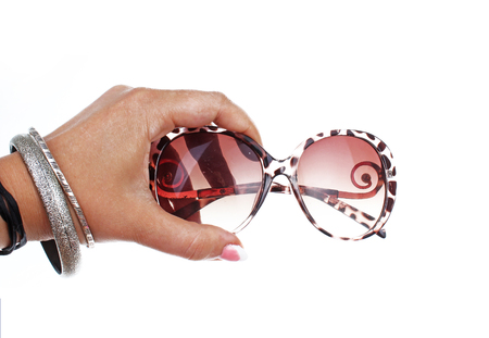 Woman hand holding sunglasses on isolated white cutout background. Studio photo with studio lighting easy to use for every concept. Stock Photo