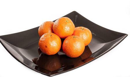 Mandarin orange. Pile of oranges mandarins on plack plate and isolated white studio background.