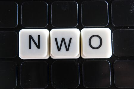 NWO text word crossword. Alphabet letter blocks game texture background. Black background. Banco de Imagens