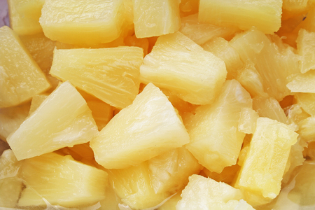 Pineapple slices as background. Yellow pineapples texture pattern.