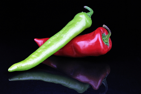 Artsy peppers red green hot strong pepper paprika on isolated black mirror mirrored reflective background.
