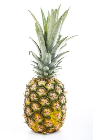 Whole pineapple on isolated white studio background.