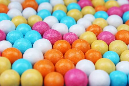 Shiny sugar coated round chocolate balls as background. Candy bonbons multicolored texture. Round candies sweets pattern concept. Food photo studio photography. Candy background Stock Photo