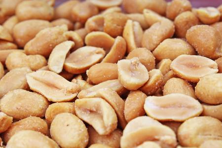 スタジオでピーナッツの背景食品写真を皮をむいた。マクロピーナッツの写真をクローズアップします。美しい塩漬けローストピーナッツパターン