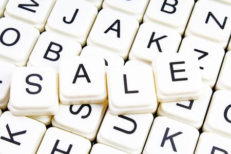 Sale text word crossword. Alphabet letter blocks game texture background. White alphabetical cubes blocks letters on crossword letters educational toy background.