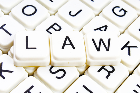 Law text word crossword. Alphabet letter blocks game texture background. White alphabetical cubes blocks letters on crossword letters educational toy background.