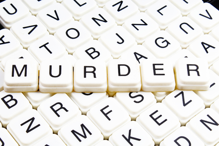 Murder text word crossword. Alphabet letter blocks game texture background. White alphabetical cubes blocks letters on crossword letters educational toy background.