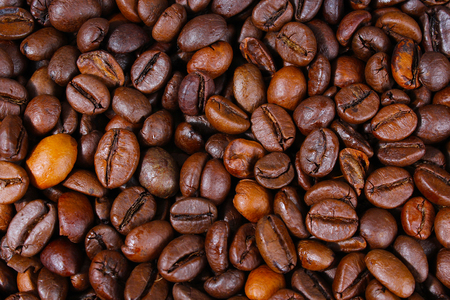 Coffee texture. Roasted coffee beans as background wallpaper. Beautiful arabica real cofee bean illustration for any concept. Gourmet coffee beans macro closeup studio photo. Stock Photo