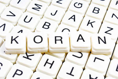 Koran text word crossword. Alphabet letter blocks game texture background. White alphabetical cubes blocks letters on crossword letters educational toy background.