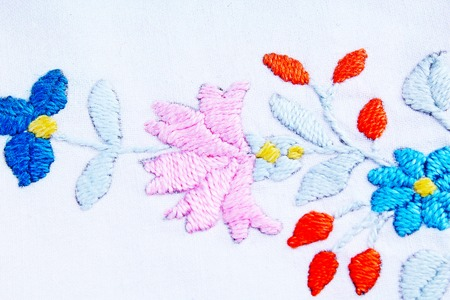 Embroidery background. Floral handwork hobby closeup photo.