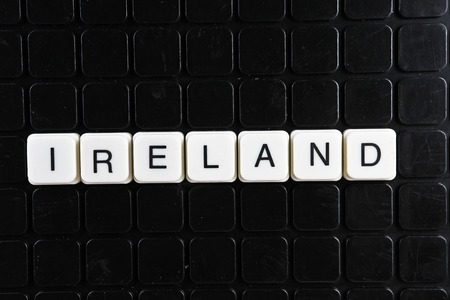 Ireland text word crossword. Alphabet letter blocks game texture background. White alphabetical letters on black background. White educational toy block with words.