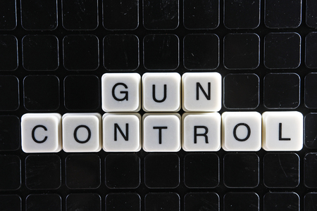 Gun control text word crossword. Alphabet letter blocks game texture background. White alphabetical letters on black background. White educational toy block with words. Banco de Imagens