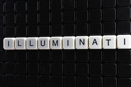 Illuminati text word crossword. Alphabet letter blocks game texture background. White alphabetical letters on black background. White educational toy block with words.