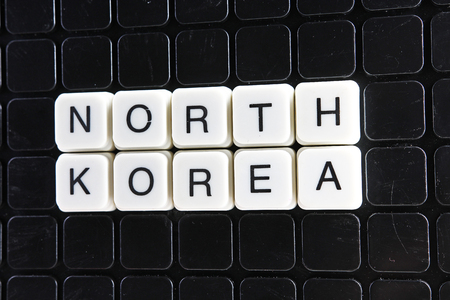 North Korea text word crossword. Alphabet letter blocks game texture background. White alphabetical letters on black background. White educational toy block with words.