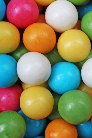 Bubble gum chewing gum texture. Rainbow multicolored gumballs chewing gums as background. Round sugar coated candy dragee bubblegum texture. Food photography. Colorful bubblegums wallpaper.