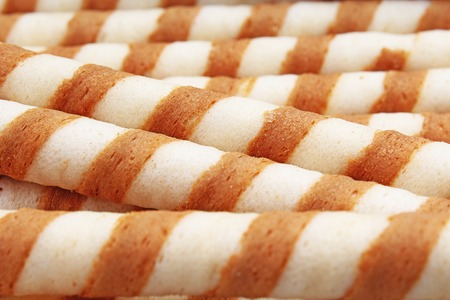 Ice cream wafer sticks as background. Wafer biscuit swirled stick texture. Wafers pattern. Stock Photo