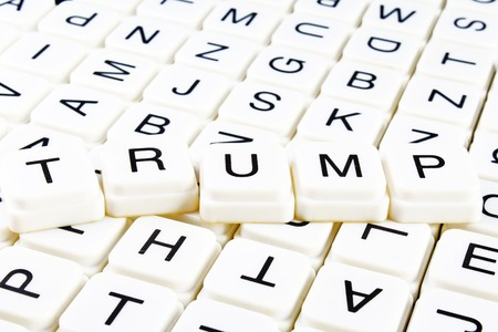Trump title text word crossword. Alphabet letter blocks game texture background. White alphabetical letters on black background. White educational toy block with words on board table.