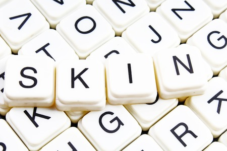 Skin title text word crossword. Alphabet letter blocks game texture background. White alphabetical letters on black background. White educational toy block with words on board table.