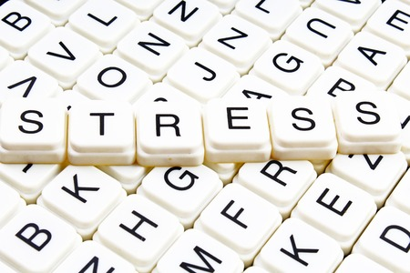 Stress title text word crossword. Alphabet letter blocks game texture background. White alphabetical letters on black background. White educational toy block with words on board table. Stock fotó