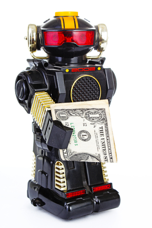 Robot on white background. Classic robot retro toy. Cute robot. Classical black plastic alloy robot with money. Electronic robotic robot holding money.