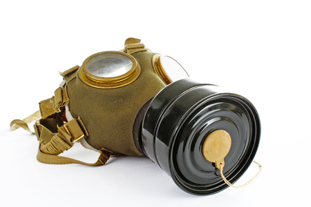 Gas mask from real war. Used vintage green and black gas mask can illustrate danger, war, catastrophe, or other concept. Gas mask on isolated white studio background. Easy to use for your work. Stock Photo